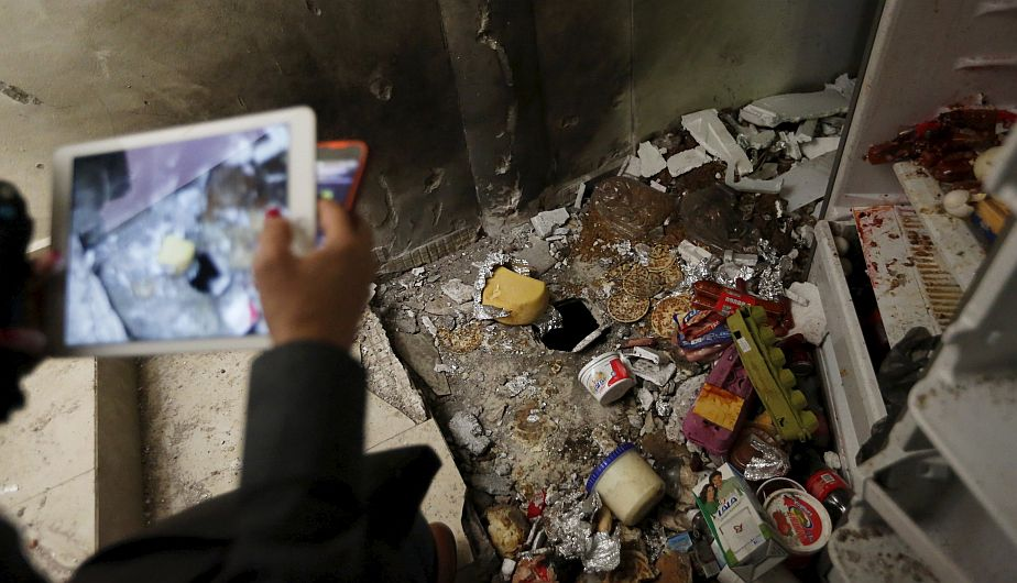 """A journalist takes photographs of scattered food items in the kitchen at a safe house, where five people were shot dead during an operation to recapture the drug lord Joaquin """"El Chapo"""" Guzman, at Jiquilpan Boulevard in Los Mochis in Sinaloa state, Mexico, January 11, 2016. REUTERS/Edgard Garrido"""